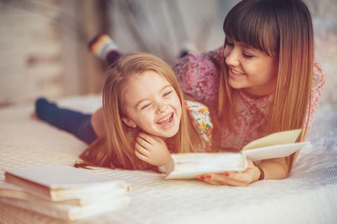 Mother and daughter laugh while reading a book together in bed