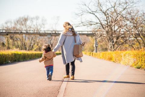 Mother and child walk down a path together at a park.