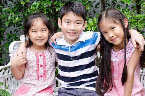 Brother wraps his arms around his two sisters as they sit outside on a bench.