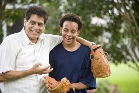 A teenager and his stepfather play catch outside.