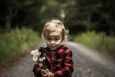 Little girl holding flowers looks playfully at the camera