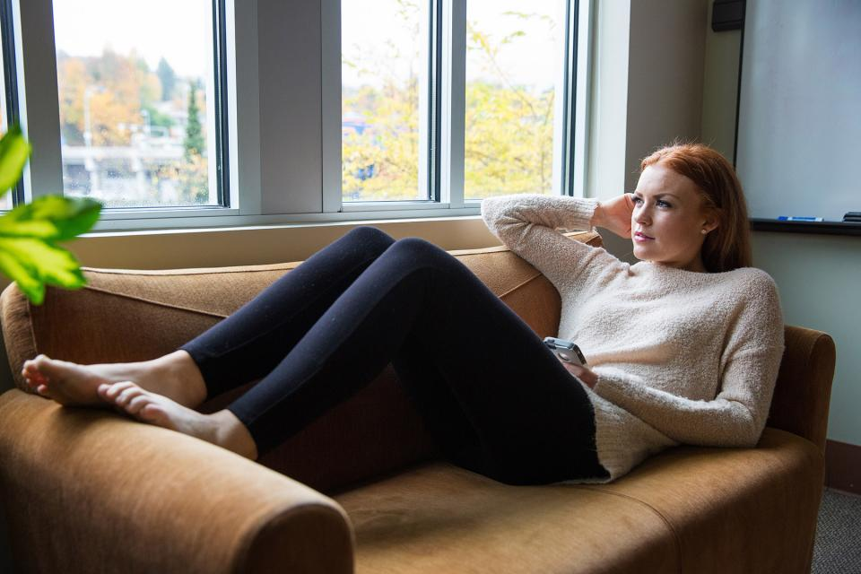 Parent reclines on couch while contemplating a message received on their phone