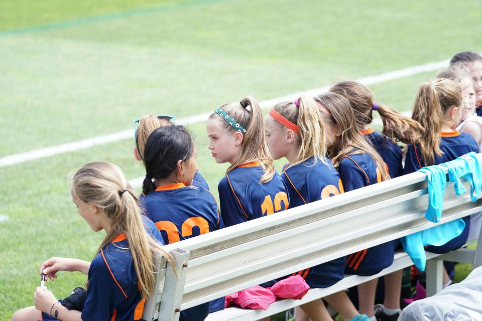 Girls sit on bench during soccer practice.