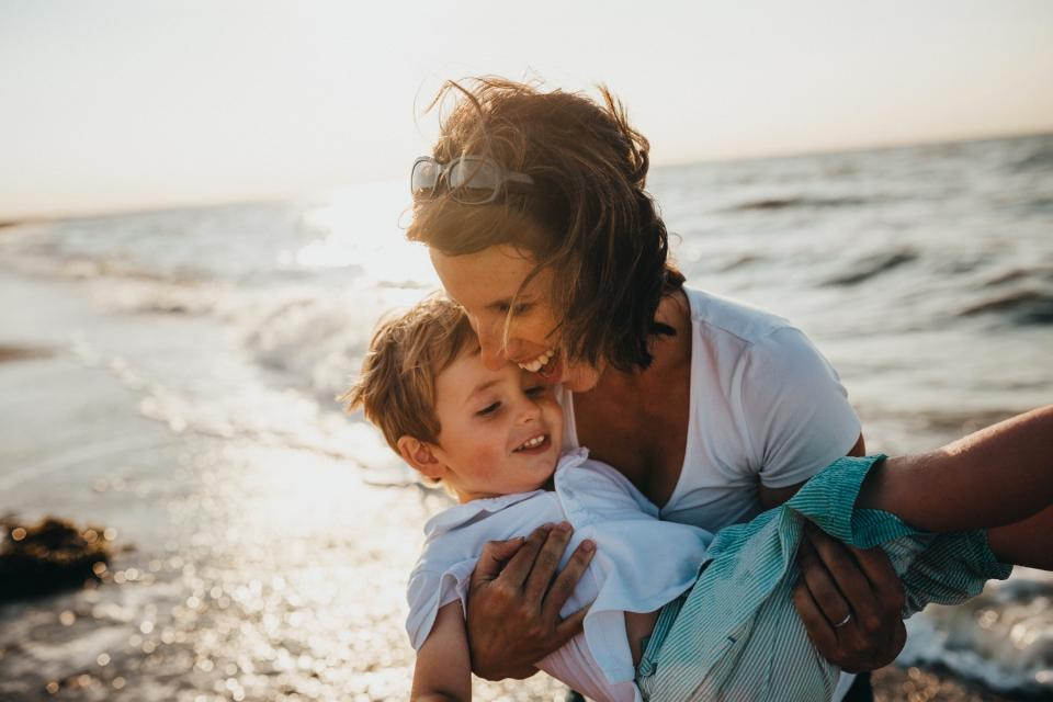 Mom and son play on the beach.