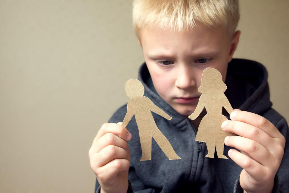 Little boy looks sadly at paper cut-outs of a mom and dad.